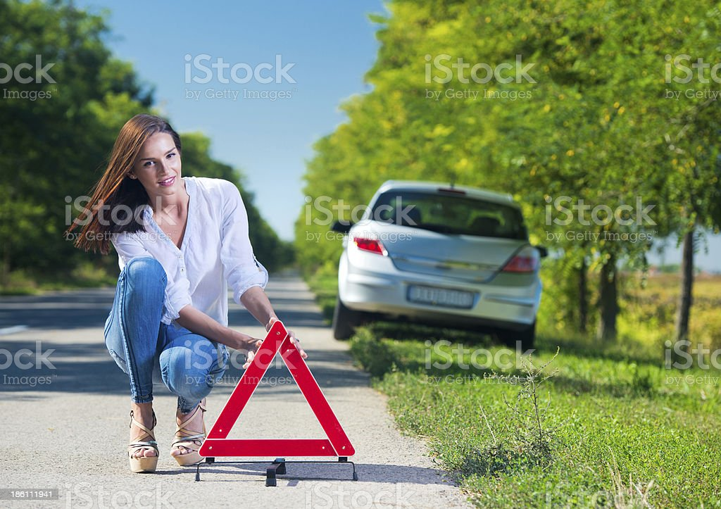 Woman putting a triangle on the road,car trouble royalty-free stock photo