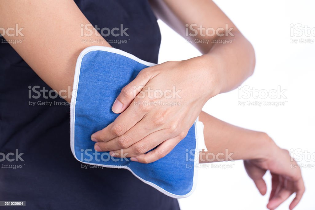 woman putting an ice pack on her elbow pain stock photo