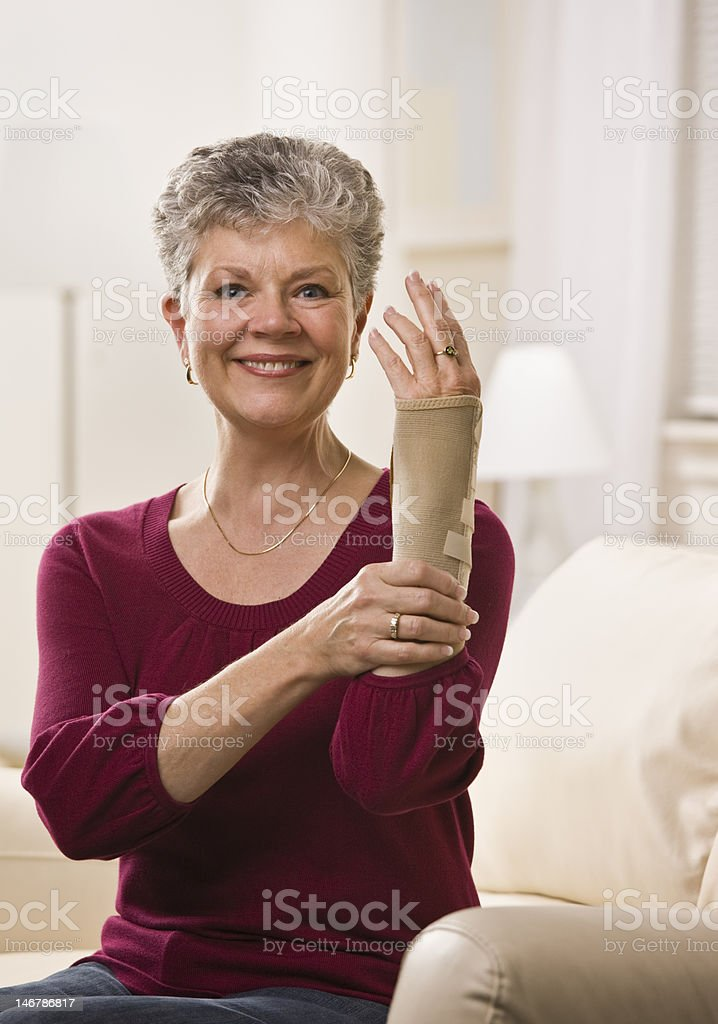 Woman Putting Brace on Hand royalty-free stock photo
