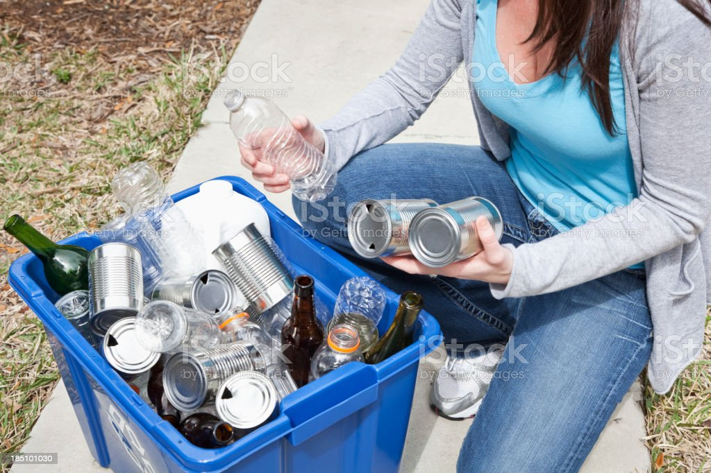 Woman putting cans and bottles in recycling bin stock photo