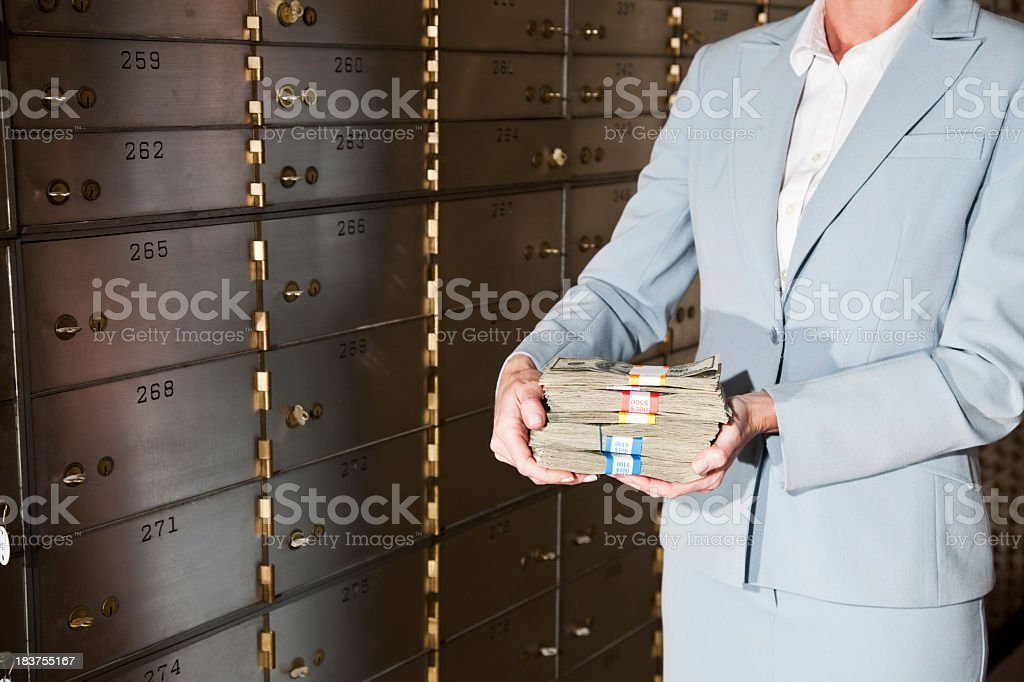 Woman putting cash in safety deposit box royalty-free stock photo