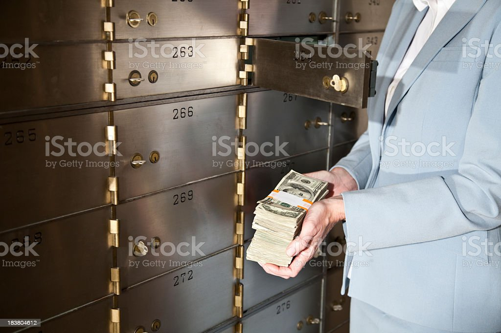 Woman putting cash in safety deposit box stock photo