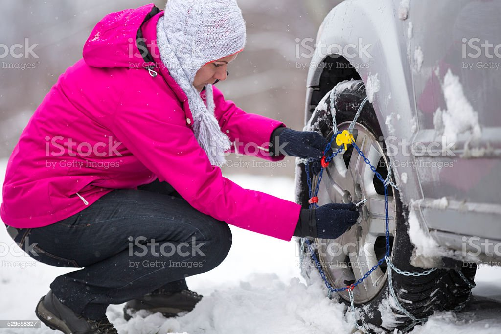 Woman putting  chain on wheels stock photo