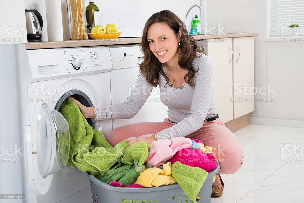 Woman Putting Clothes Into Washing Machine stock photo