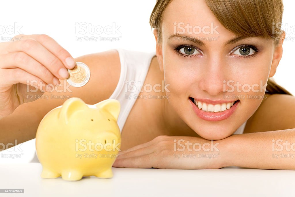 Woman putting coin in piggy bank royalty-free stock photo