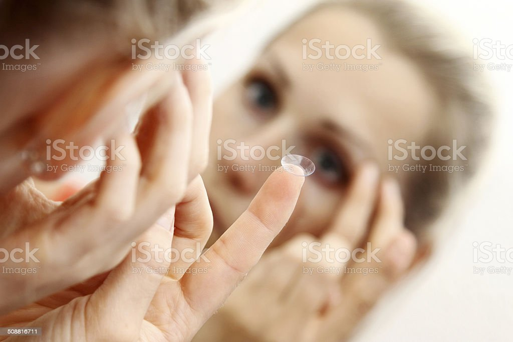 woman putting contact lens in her eye stock photo