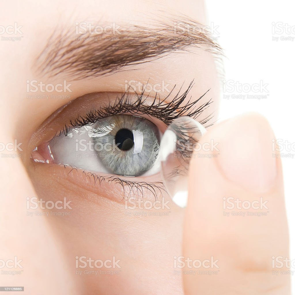 Woman putting contact lens into eye stock photo