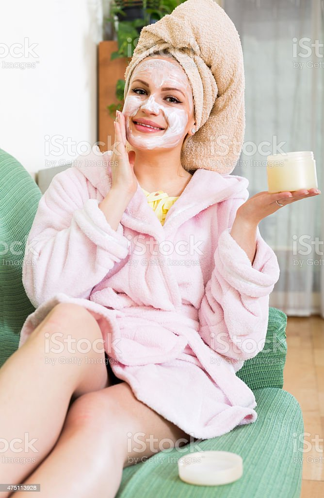 woman putting cosmetic treatment on face stock photo
