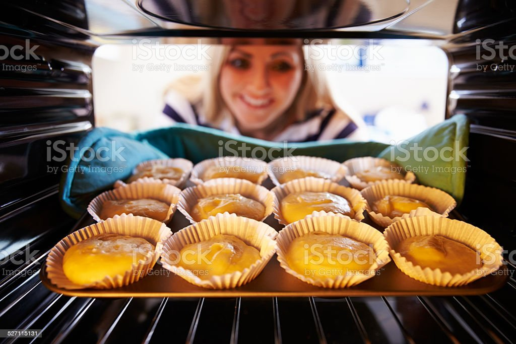 Woman Putting Cupcakes Into Oven To Bake stock photo