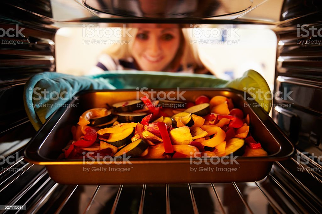 Woman Putting Dish Of Vegetables Into Oven To Roast stock photo