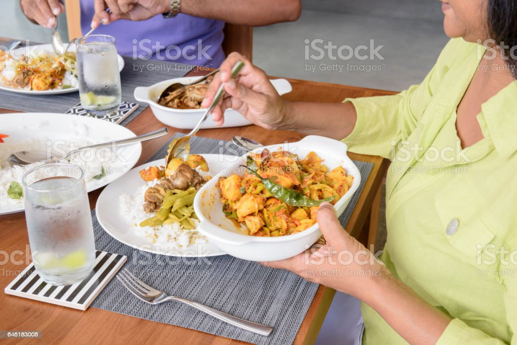Woman putting food on her plate at table stock photo