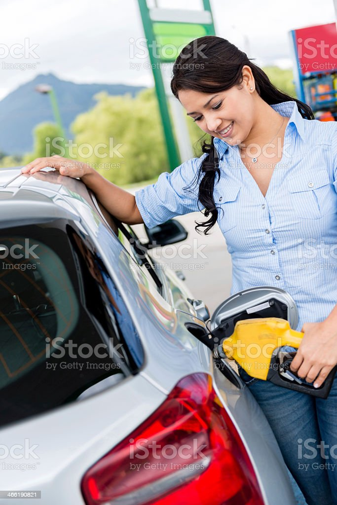Woman putting fuel in the car stock photo