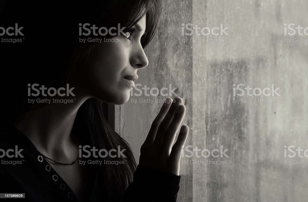 A woman putting her hand on a window and looking out royalty-free stock photo