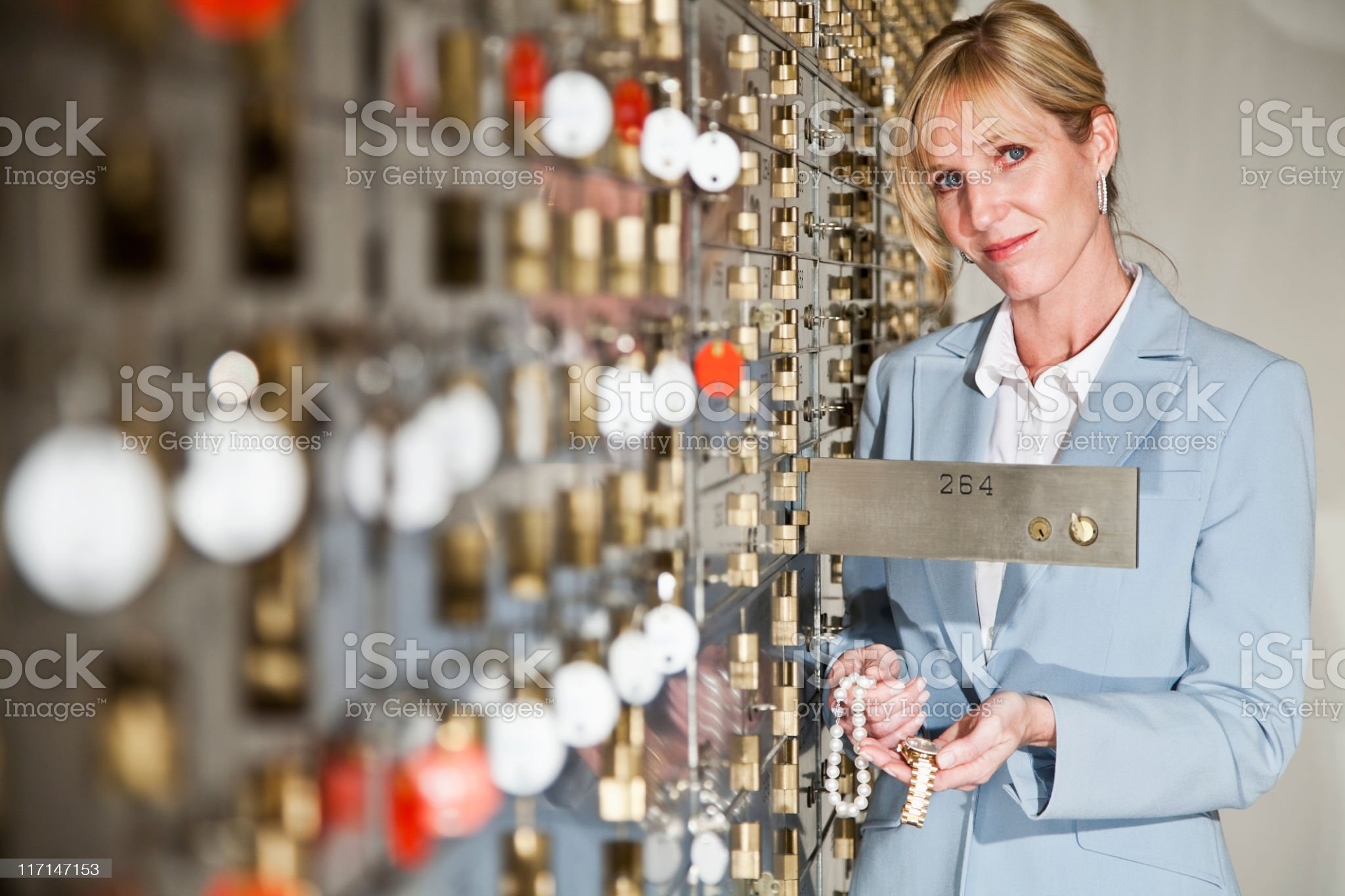 Woman putting jewelry in safety deposit box royalty-free stock photo
