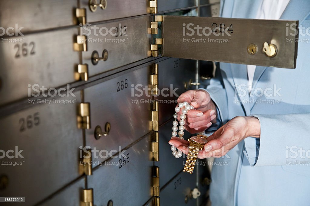 Woman putting jewelry in safety deposit box stock photo