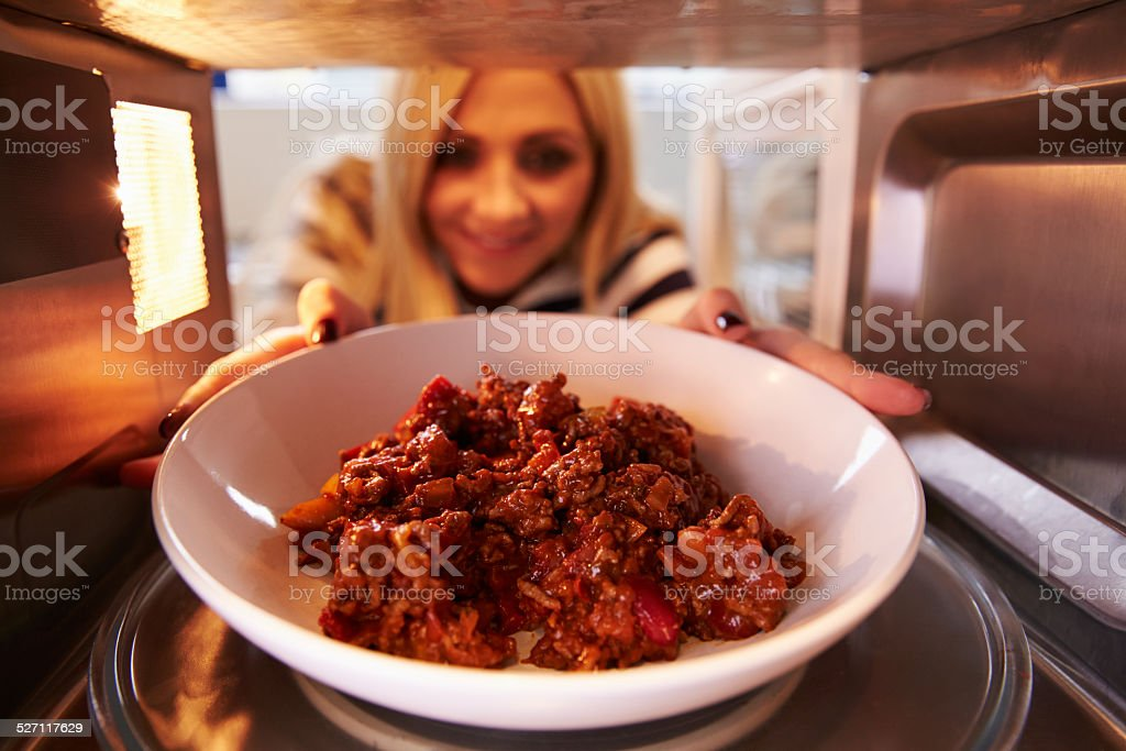 Woman Putting Leftover Chili Into Microwave Oven To Cook stock photo