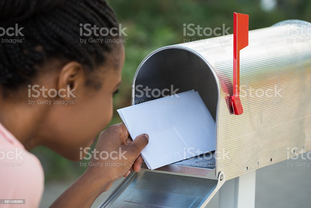 Woman Putting Letter In Mailbox stock photo