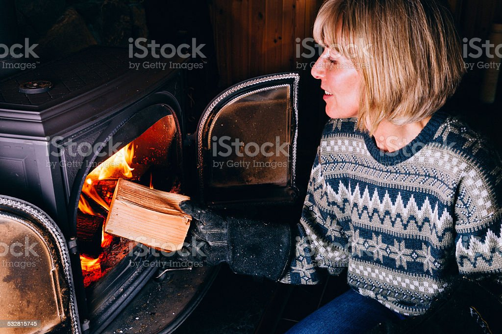 Woman putting logs in a wood burning stove stock photo