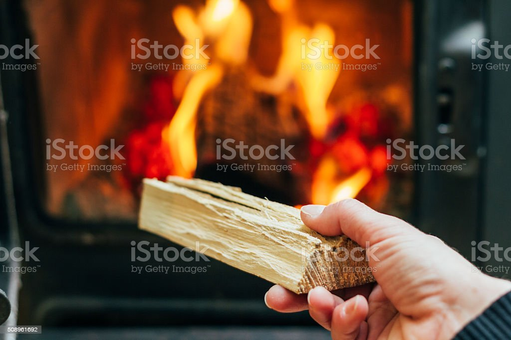 Woman Putting Logs In Fireplace stock photo