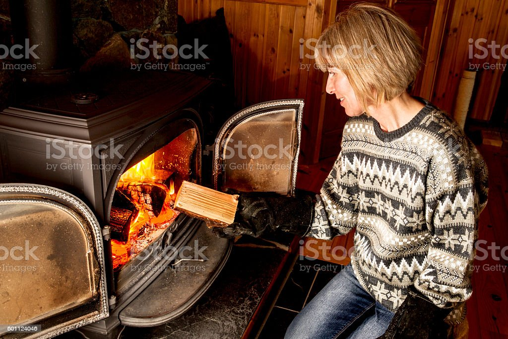 Woman putting logs in wood burning stove stock photo