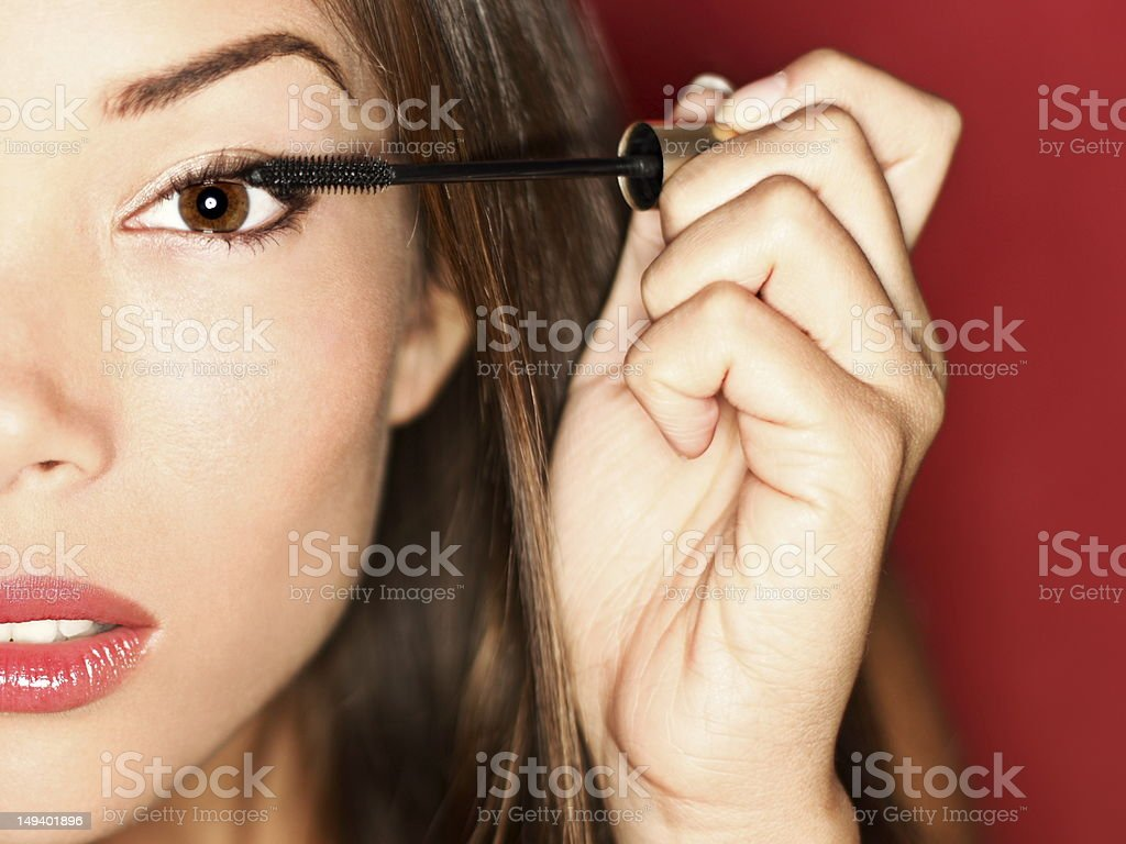 Woman putting mascara makeup stock photo