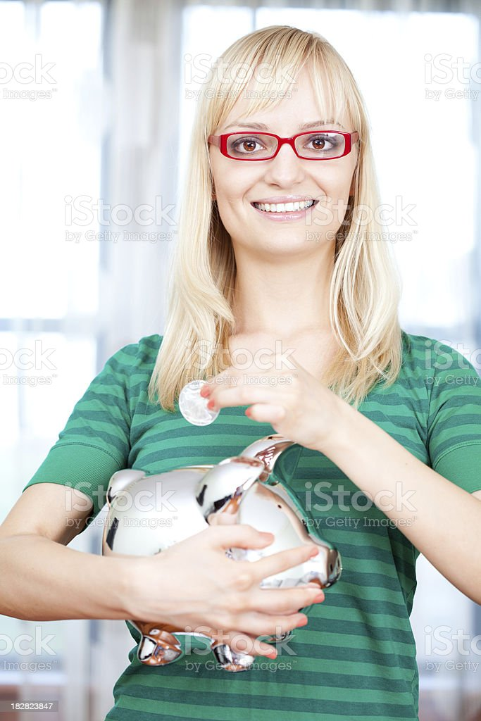 Woman putting money in piggy bank royalty-free stock photo