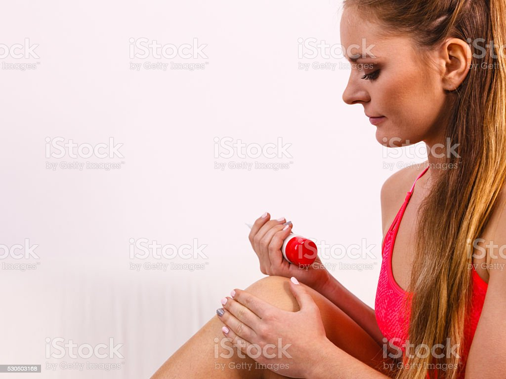 Woman putting ointment on injury knee skin care stock photo