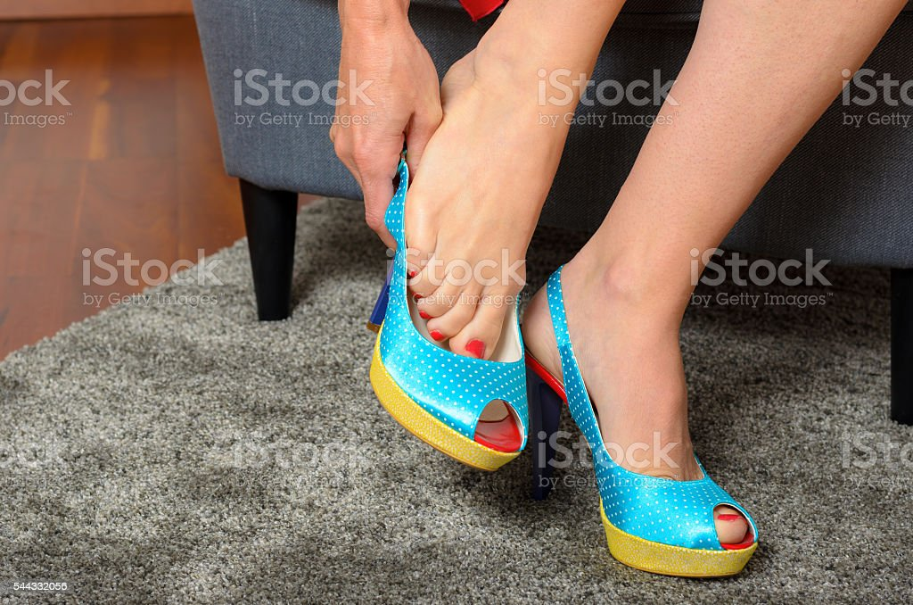 Woman putting on a pair of trendy blue shoes stock photo