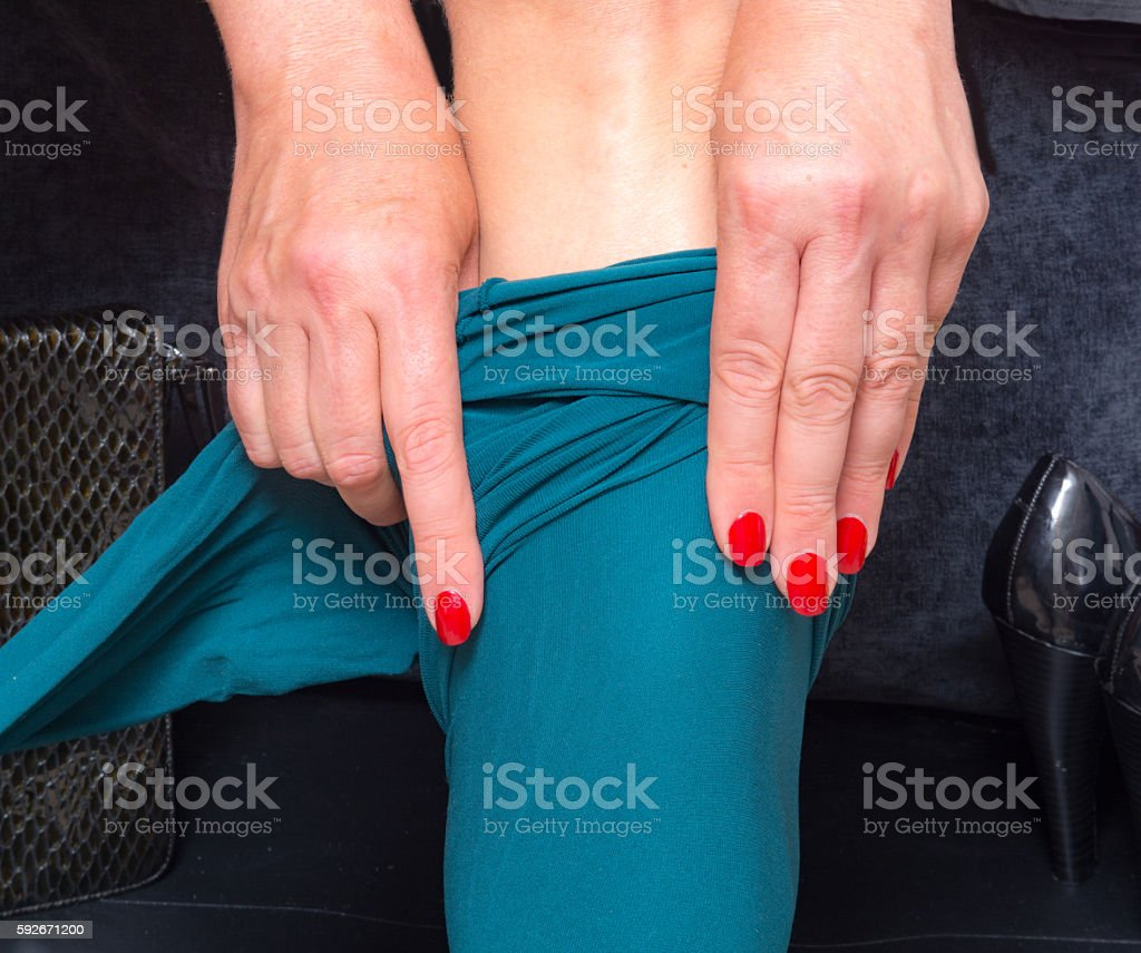 Woman putting on an opaque petrol color pantyhose stock photo