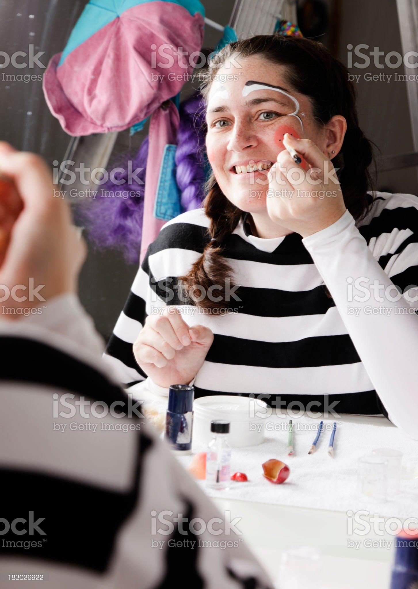 Woman Putting on Clown Makeup royalty-free stock photo