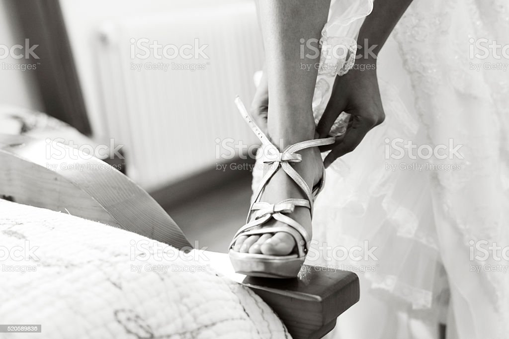 Woman putting on her right sandal (high heel wedding shoe) stock photo