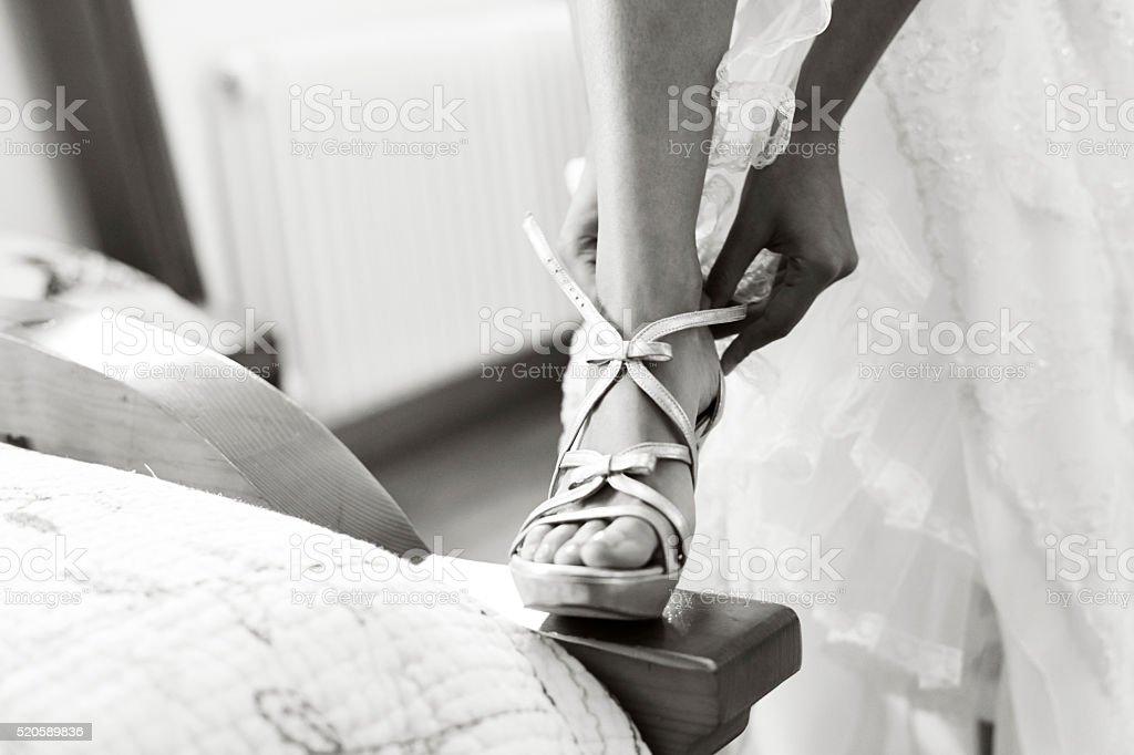 Woman putting on her right sandal (high heel wedding shoe) stock photo