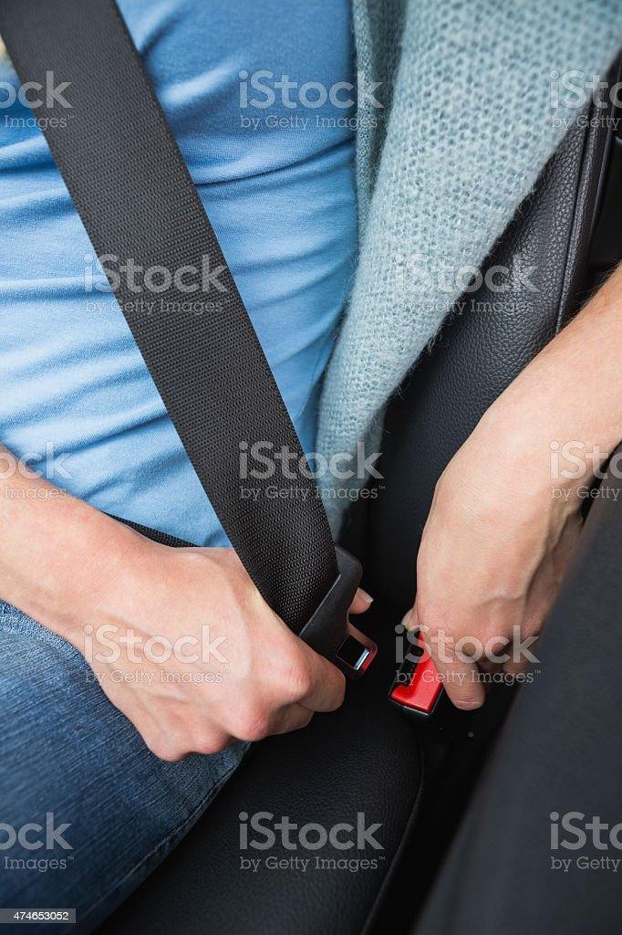 Woman putting on her seat belt stock photo