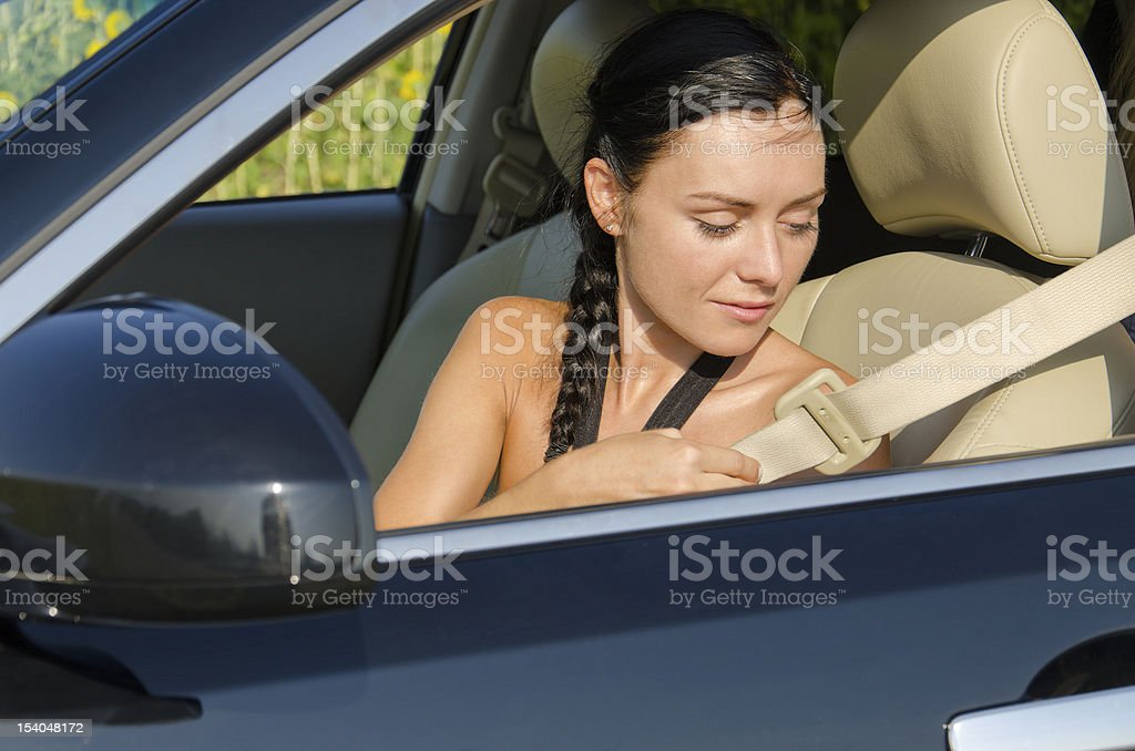 Woman putting on her seatbelt stock photo