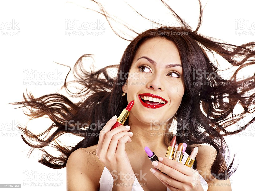 Woman putting on lipstick in wind  stock photo