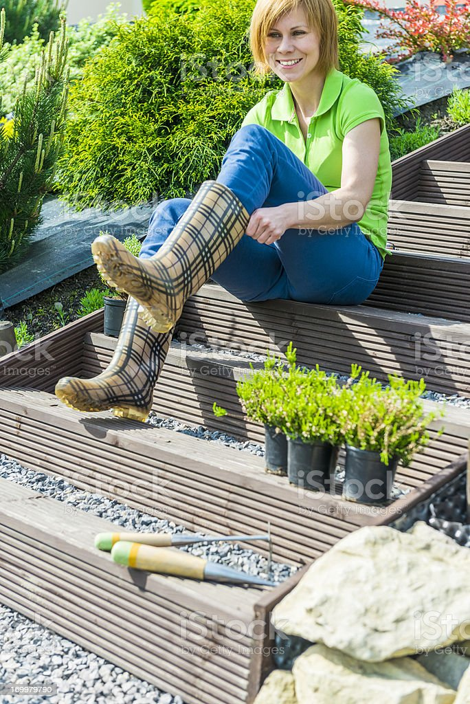 Woman putting on rubber boots, starting working garden, planting seedlings royalty-free stock photo