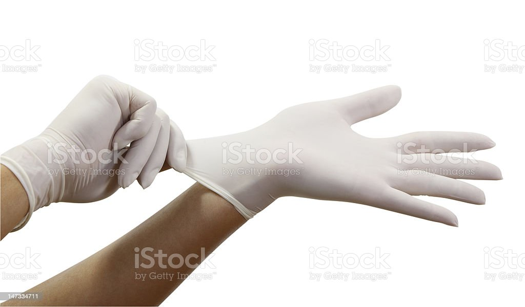 Woman putting on surgical gloves stock photo