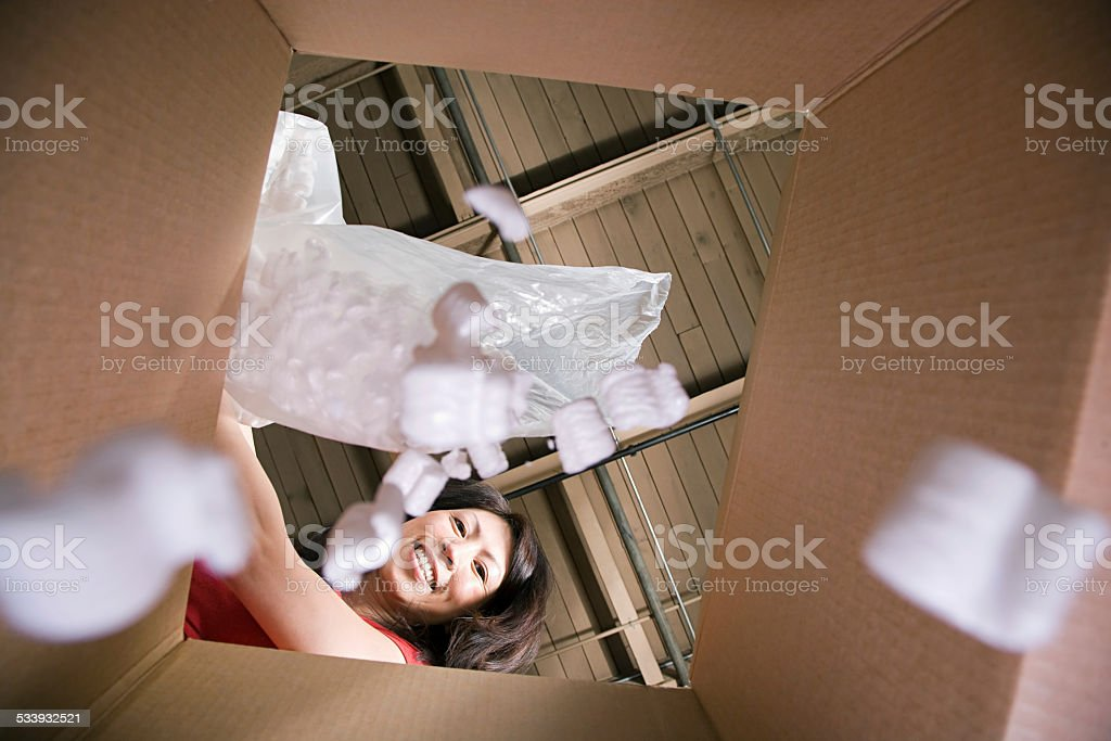 Woman putting packing peanuts in box stock photo