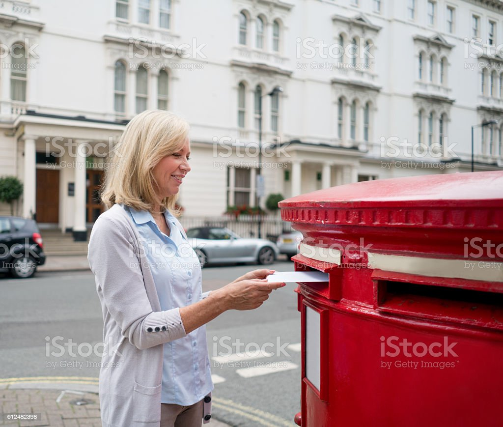 Woman putting postcard in the mailbox stock photo