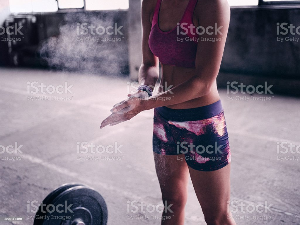 Woman putting powder on her hands preparing for lifting weights stock photo