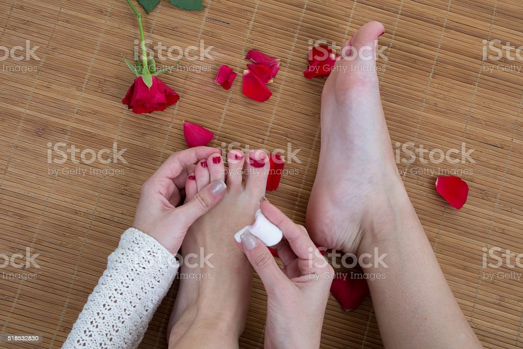 Woman putting red nail polish on her toe nails stock photo