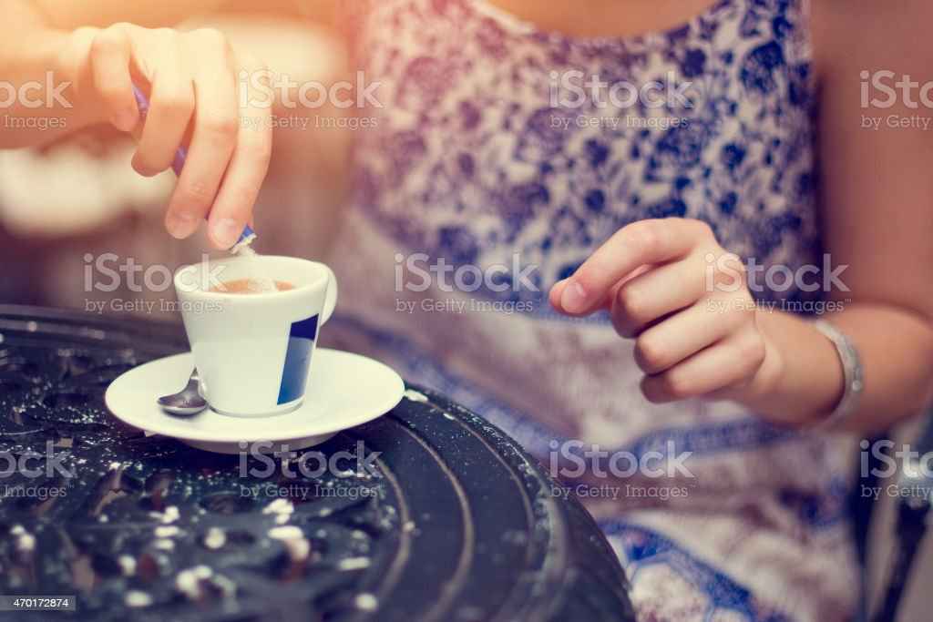 Woman putting sugar in the coffee stock photo
