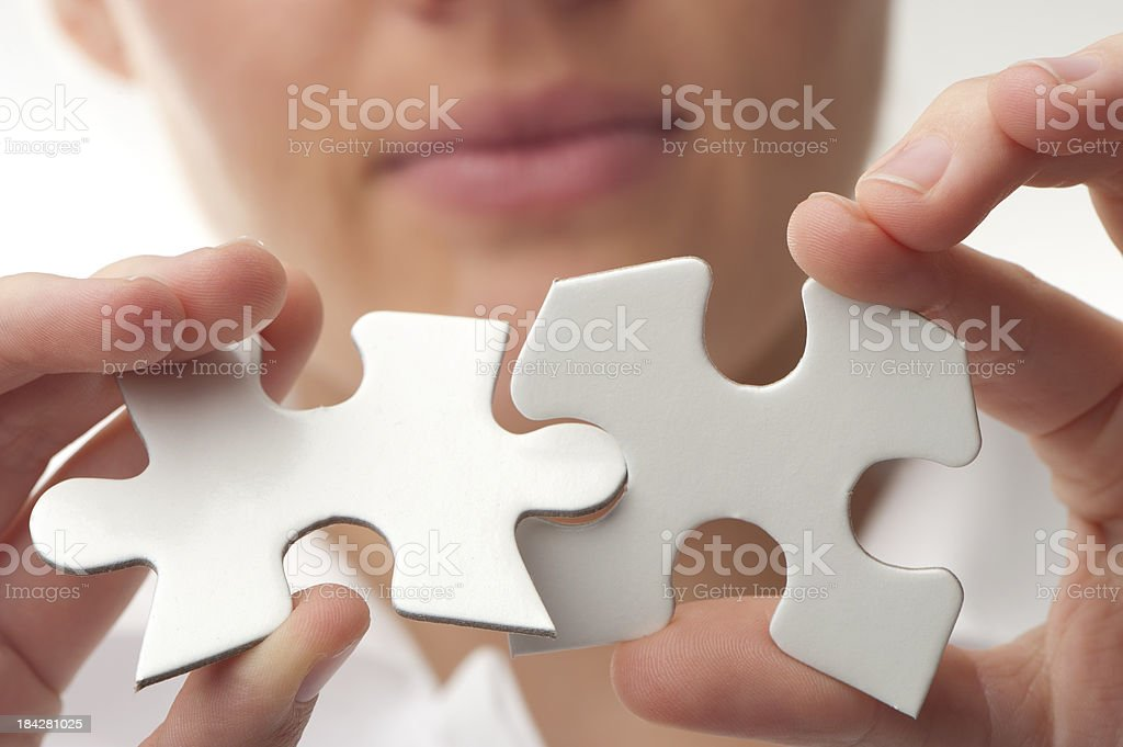 Woman putting together jigsaw puzzle pieces royalty-free stock photo