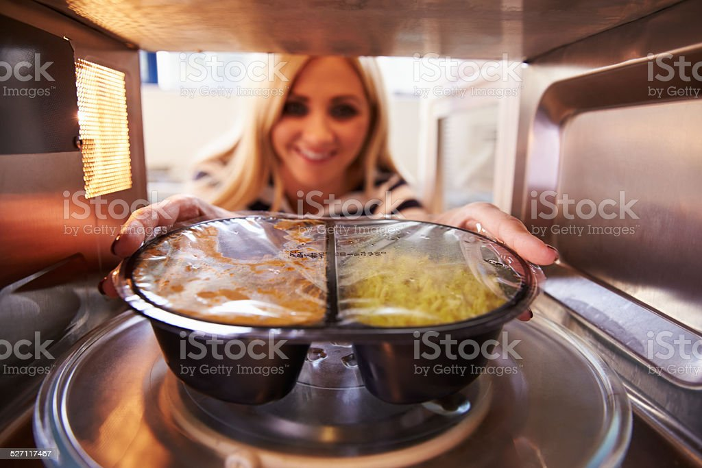 Woman Putting TV Dinner Into Microwave Oven To Cook stock photo