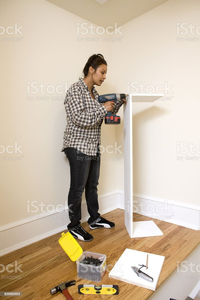 Woman putting up shelves in closet stock photo
