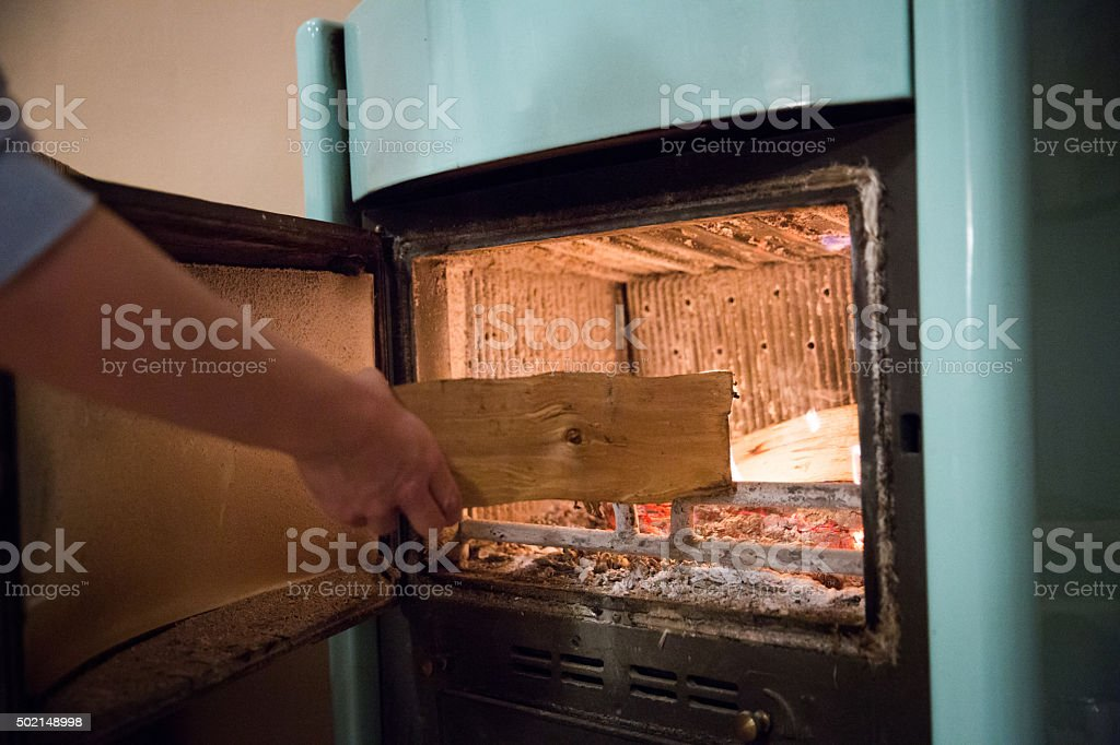 Woman putting wood on a wood burning stove stock photo