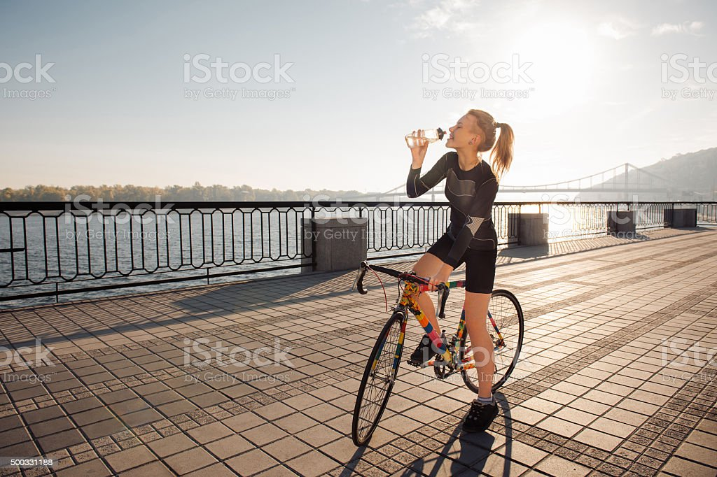 Woman quenches thirst while riding a bike stock photo