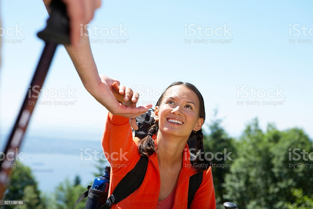 Woman reaching hand up for help while climbing stock photo