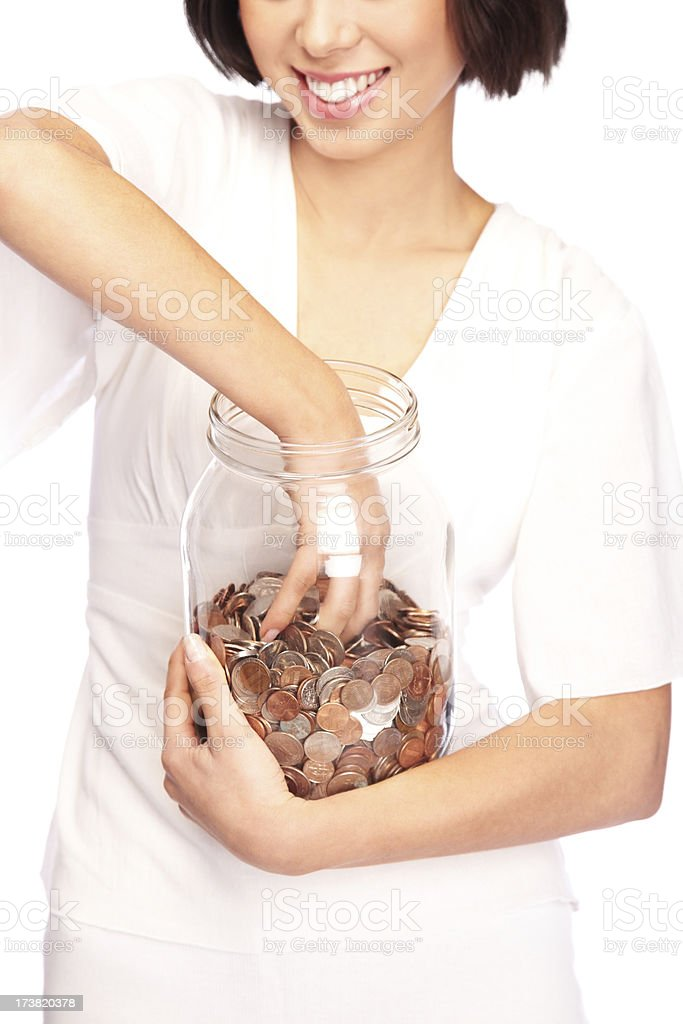 Woman Reaching Into a Jar of Coins stock photo