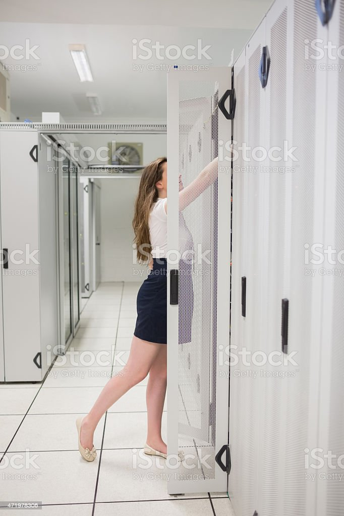 Woman reaching into servers stock photo